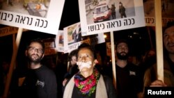 "Israeli left wing demonstrators march holding placards protesting the right wing incitement against President Reuven Rivlin and human rights activists in Tel Aviv. December 19, 2015. An ultra-nationalist Israeli group has published a video accusing the heads of four of Israel's leading human rights organisations of being foreign agents funded by Europe and supporting Palestinians ""involved in terrorism"". The sign reads, ""That's how occupation looks like."""