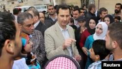 Presiden Suriah Bashar al-Assad (tengah) berbincang dengan warga saat berkunjung ke desa Ein al-Tinah, timur laut Damaskus (20/4).