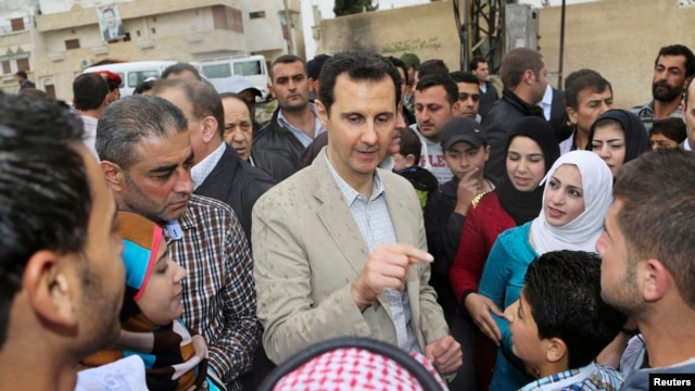 Syrian President Bashar al-Assad chats with people during his visit to Ein al-Tinah village, northeast of Damascus, April 20, 2014.