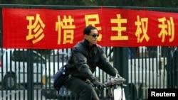 一名北京男子骑车从敦促市民积极参加地方选举的标语前路过。(资料照片)