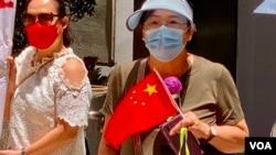 有白衣人支持者手持迷你中國國旗(美國之音湯惠芸)
