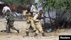 Somali government soldiers open fire during an ambush by al-Shabaab rebels on the outskirts of Elasha town, May 29, 2012.