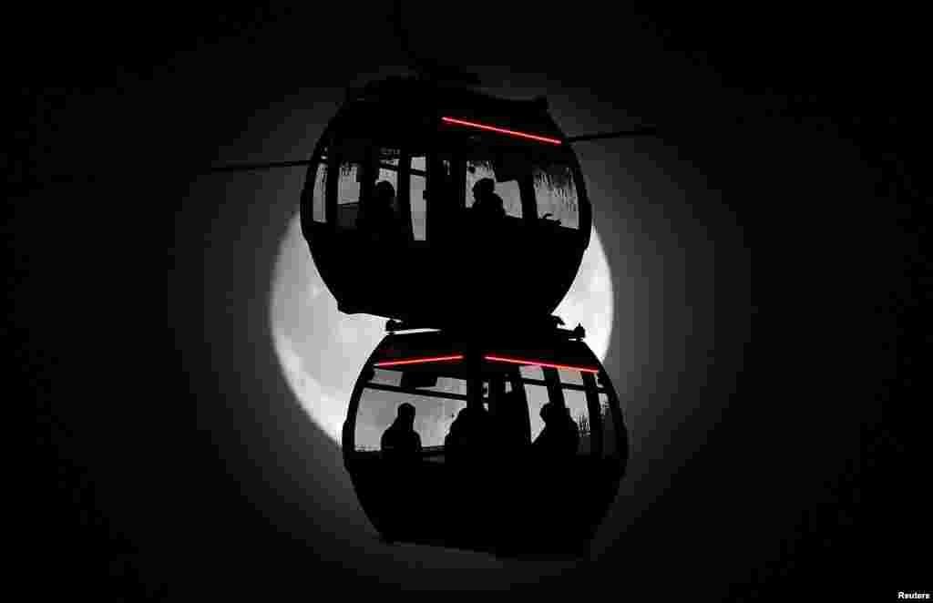 Siluet para penumpang saat mereka naik kereta gantung Emirates Airline, sementara bulan tampak di latar belakang, di atas Sungai Thames di London, Inggris.