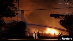 Firefighters look at a train wagon on fire at Lac Megantic, Quebec, July 6, 2013.
