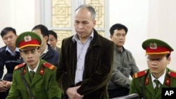 Dissident blogger Pham Viet Dao, standing at center, appears at a court in Hanoi, Vietnam Wednesday March 19, 2014.
