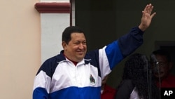 Venezuela's President Hugo Chavez waves to supporters from Miraflores presidential palace at an event marking the 10th anniversary of his return to power after a failed coup in Caracas, Venezuela, April 13, 2012.