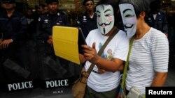 FILE - Anti-government protesters wearing Guy Fawkes masks use an iPad in front of riot policemen during a rally outside a shopping mall in Bangkok, June 9, 2013.