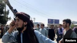 一名塔利班武装人员在喀布尔卡尔扎伊国际机场外巡逻(路透社2021年8月16日)