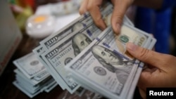 Nhân viên ngân hàng đếm đồng đô la Mỹ tại một chi nhánh ngân hàng ở Hà Nội ngày 16/5/2016.