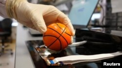 Dr. Benjamin Tee, Assistant Professor of Materials Science and Engineering at the National University of Singapore (NUS), demonstrates how his device can detect the texture of a soft stress ball at a lab in NUS, Singapore July 27, 2020. (REUTERS/Joseph Campbell)