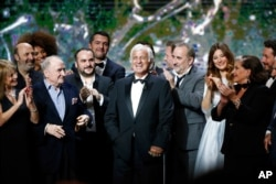 FILE - French actor Jean-Paul Belmondo, center, is congratulated by actors on stage during the ceremony of the 42nd Cesar Film Awards, at the Salle Pleyel, in Paris, Feb. 24, 2017.