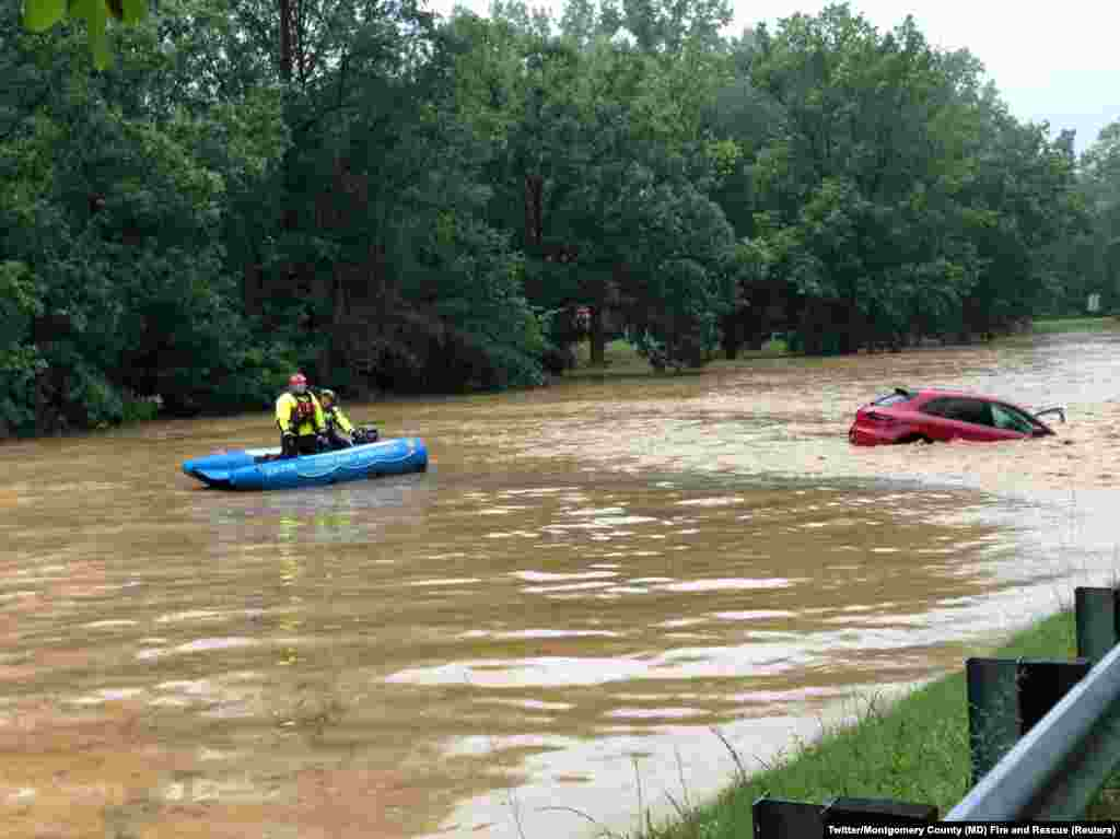 Crew of a water rescue vessel is seen near a car in flood waters on Clara Barton Parkway near Washington, D.C., July 8, 2019 in this picture obtained from social media.