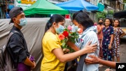 An anti-coup student protester is welcomed home with flowers by the residents of her neighborhood after being released from jail, in Yangon, Myanmar.