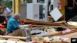 Un anciano descansa mientras busca recuerdos en su destruida casa en Tupelo, Mississippi.