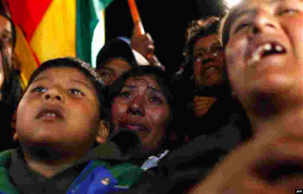 Relatives of trapped Bolivian miner Carlos Mamani Solis react while watching his rescue on a TV screen at the camp outside the San Jose mine near Copiapo, Chile, early Wednesday, Oct. 13, 2010. (AP Photo/Natacha Pisarenko)