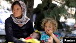 Keluarga yang mengungsi dari kaum minoritas Yazidi, menghindari kekerasan di kota Sinjar, Irak, menunggu makanan ketika beristirahat di perbatasan Irak-Suriah di Fishkhabour, provinsi Dohuk 13 Agustus 2014.