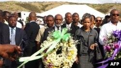 Tổng thống Haiti Rene Preval (giữa), phu nhân Elisabeth Delatour cùng Thủ tướng Jean-Max Bellerive (phải) chuẩn bị đặt vòng hoa tại St. Christophe, nơi chôn cất hàng ngàn nạn nhân của trận động đất
