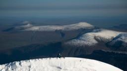 Peneliti Ninis Rosqvist di puncak selatan Kebnekaise di Swedia tampak menggunakan peralatan untuk melakukan pengukuran ketinggian gunung es. Ketinggian gunung-gunung es di Swedia menyusut dengan cepat akibat mencairnya lapisan gletser karena pemanasan global.