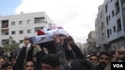 Para demonstran menggotong jenazah seorang aktivis yang tewas Jumat, pada prosesi pemakaman di Quabon, dekat Damaskus, Sabtu (23/4).