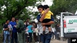 Famílias atravessam a fronteira entre o México e os EUA, enquanto a polícia de fronteira confere os seus documentados