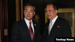 25일 라오스 비엔티안에서 열린 북-중 양자회담에 앞서 중국 왕이 외교부장(왼쪽)이 북한 리용호 외무상과 악수하고 있다.