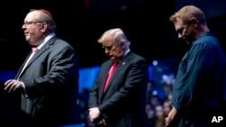 Desde la izquierda, el rabino Benjamin Sendrow acompañado por el presidente Donald Trump y el pastor Thom O'Leary, oran en la Convención y Exposición Agricultores del Futuro en Bankers Life Fieldhouse en Indianapolis, el 27 de octubre de 2018.