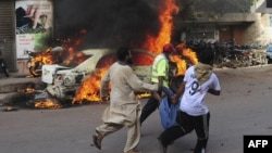 Pakistani volunteers and local residents carry the dead body of a protester beside a burning car after gunmen opened fire on a rally in Karachi, May 22, 2012.