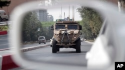 A patrolling U.S. armored vehicle is reflected in the mirror of a car in Kabul, Afghanistan, Aug. 23, 2017.