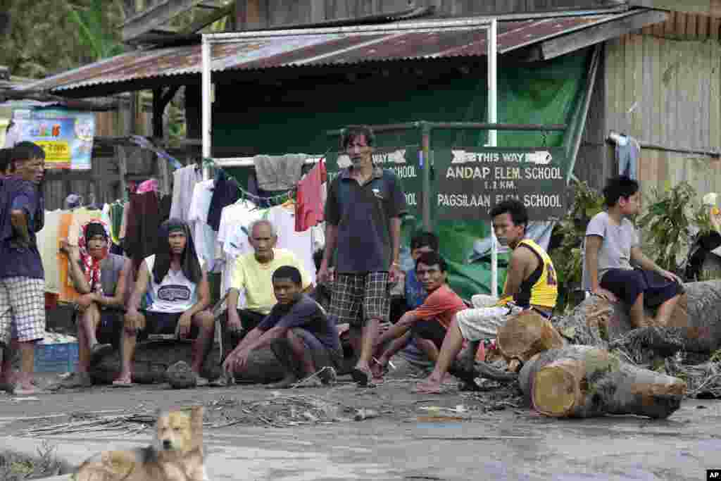 Residents wait for relief supplies at the flash flood-hit village of Andap, New Bataan township, Compostela Valley in southern Philippines, December 5, 2012, a day after the devastating Typhoon Bopha made landfall.