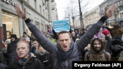 FILE - In this Sunday, Jan. 28, 2018 file photo, Russian opposition leader Alexei Navalny, center, attends a rally in Moscow, Russia. (AP Photo/Evgeny Feldman, File)