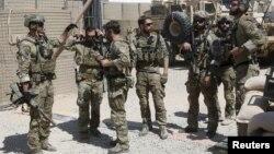ກຳລັງພິເສດຂອງສະຫະລັດ ໂອ້ລົມກັນ ກ່ອນອອກຈາກຄ້າຍ ທີ່ແຂວງ Helmand ໃນພາກໃຕ້ ອັຟການິສຖານ. (28 ກັນຍາ 2015)