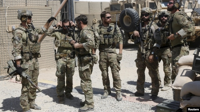 FILE - U.S. special forces soldiers consult before leaving their base in Helmand, Afghanistan Sept. 28, 2015.