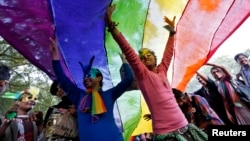 FILE - Participants dance under a a rainbow flag as they attend the sixth Delhi Queer Pride parade, an event promoting gay, lesbian, bisexual and transgender rights, in New Delhi.