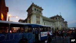 Manifestantes se acercan a un autobús dañado por manifestantes frente al Palacio Nacional para exigir la renuncia del presidente Alejandro Giammattei, en la Ciudad de Guatemala, el sábado 28 de noviembre de 2020.