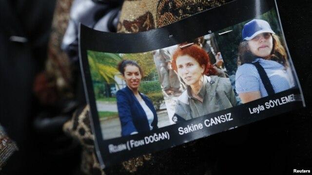 Hình ba nạn nhân được đính trên áo khoác của một thành viên cộng đồng người Kurd khi cộng đồng này tập trung bên cạnh cổng vào Trung tâm Thông tin người Kurd ở Paris, France, 10/1/2013. ( REUTERS/Christian Hartmann)