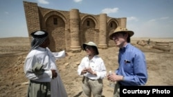 Laurie Rush and colleague Brian Rose at the ancient city of Uruk in Iraq, talking with Mr. Altubi, head of the family that protects the site. (Courtesy Laurie Rush)