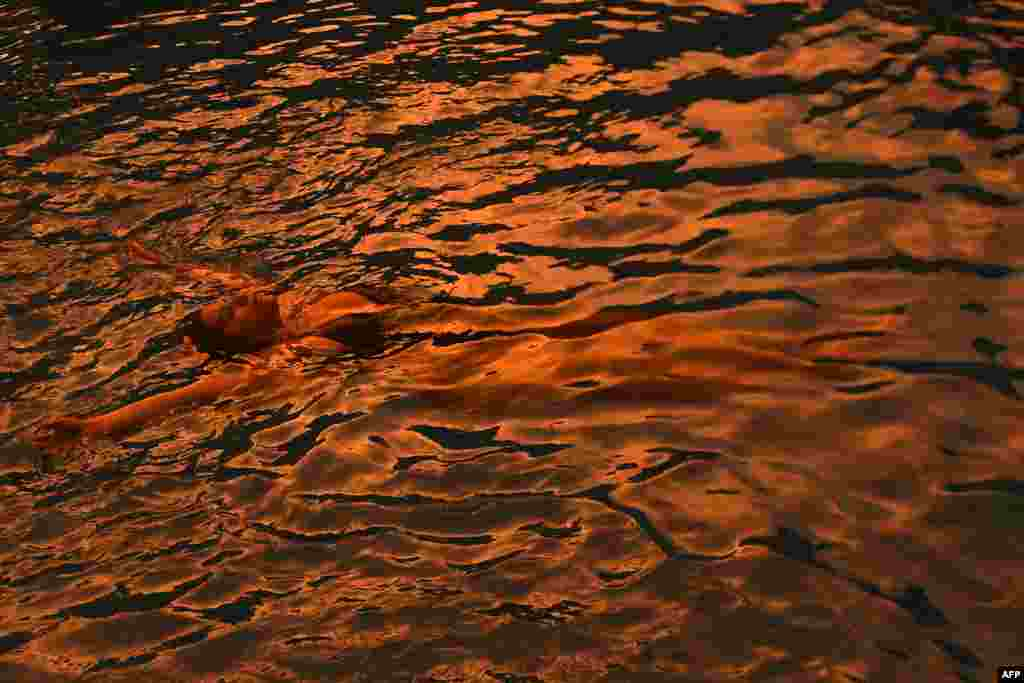 A woman cools off in a swimming pool during the last rays of sunlight in San Jose Villanueva, 25 km southwest of San Salvador on September 3, 2017.