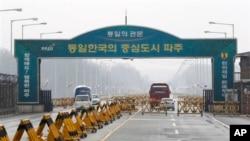 Kendaraan Korea Selatan (kiri) melintasi jembatan unifikasi di Paju, Korea Selatan dari kawasan industri Kaesong di Korea Utara (6/4). Korea Utara akan memutuskan penghubung terakhirnya dengan Seoul, dengan menarik 50 ribu pekerjanya keluar dari Kaesong, Senin (8/4).