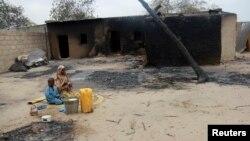 尼日利亞一名婦女及小孩在一間焚燒後的屋外。