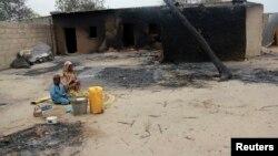 Seorang ibu dan anaknya duduk di luar rumah yang terbakar hangus akibat konflik antara pasukan Nigeria dan militan di Nigeria utara (foto; dok).