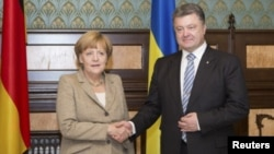 우크라이나를 방문중인 앙겔라 메르켈 독일 총리가 23일 수도 키예프에서 페트로 포로셴코 우크라 대통령과 악수하고 있다.