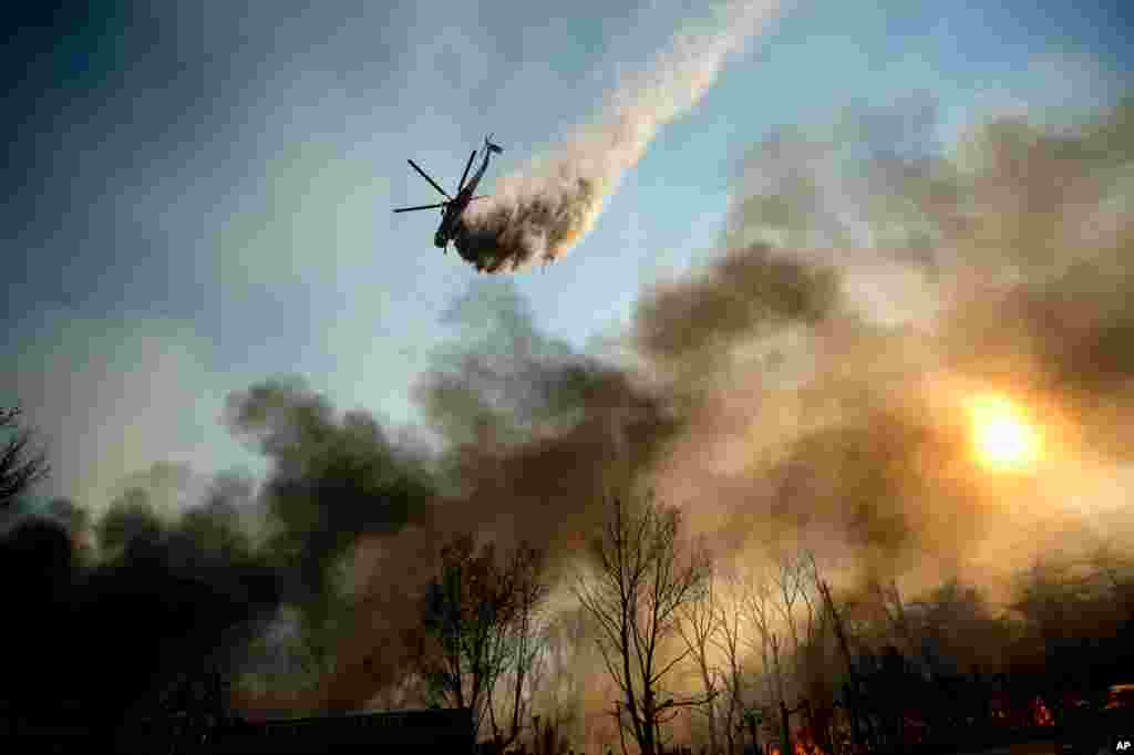 A helicopter drops water on a wildfire as it burns through Keenbrook, Calif., on Wednesday, Aug. 17, 2016.