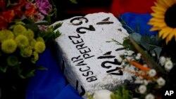 Flores rodean un ladrillo blanco que identifica la tumba del policía rebelde Óscar Pérez, después que fuera sepultado en forma controlada en un cementerio de Caracas, Venezuela, el domingo, 21 de enero de 2018.