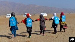 Afghan schoolgirls hold hands and walk towards their tent classrooms on the outskirts of Jalalabad, capital of Nangarhar province, Dec. 13, 2016.