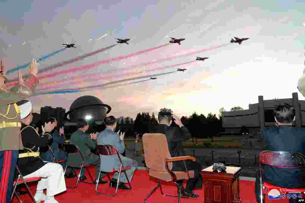 """North Korean leader Kim Jong Un, 2nd right, watches a demonstration flight during the opening ceremony of the defense development exhibition """"Self-Defence-2021"""" in Pyongyang, in this picture taken October 11, 2021, and released from North Korea's official Korean Central News Agency on October 12."""