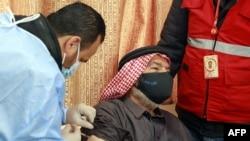 Seorang pengungsi Suriah di Yordania menerima suntikan vaksinasi COVID-19 di pusat kesehatan pemerintah di Mafraq, utara Yordania, 18 Januari 2021.