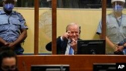 Ratko Mladic berusaha melucu dengan meniru wartawan yang mengambil fotonya di Den Haag, Selasa (8/6).
