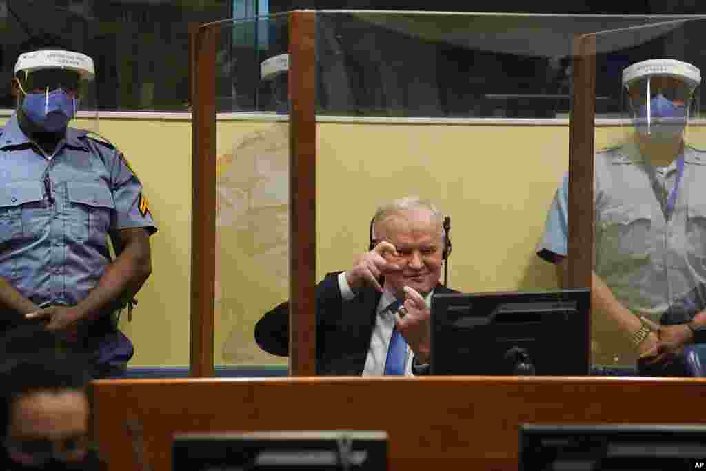 Former Bosnian Serb military chief Ratko Mladic imitates taking pictures as he sits the courtroom in The Hague, Netherlands, where the U.N. court delivers its verdict in the appeal of Mladic against his convictions for genocide and other crimes in the Bos