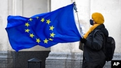 An anti-Brexit demonstrator holds an EU flag in Parliament Square, in London, Dec. 16, 2020.