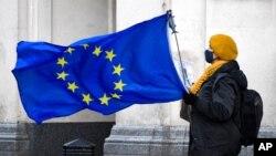 ຜູ້ປະທ້ວງຕໍ່ຕ້ານ Brexit ຖືທຸງຂອງສະຫະພາບຢູໂຣບ ຫຼື EU ຢູ່ໃນຈັດຕຸລັດ ຂອງສະພາ (Parliament Square), ໃນນະຄອນຫຼວງລອນດອນ ຂອງອັງກິດ, ວັນທີ 16 ທັນວາ 2020.